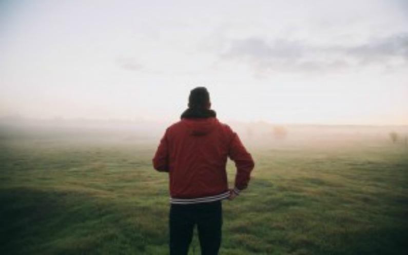 霧の中を赤いジャケットの男性が行く
