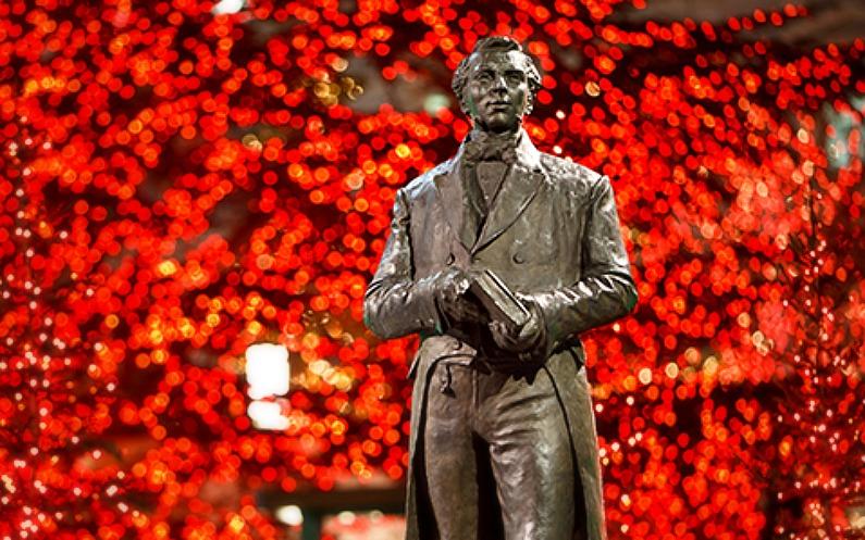 赤のクリスマスライトを背景に立つジョセフ・スミスの像