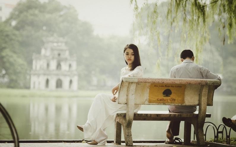 喧嘩をしていてそっぽを向いてベンチに座るカップル