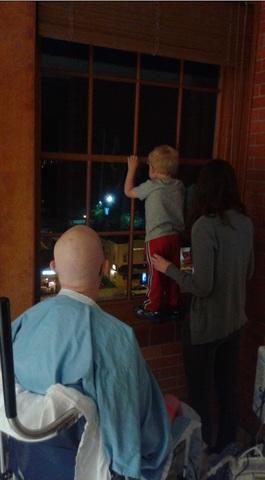 がんで髪の毛が抜けてしまった父親とその家族が夜景を窓から見る