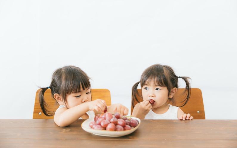 フルーツを一緒に食べる子供たち