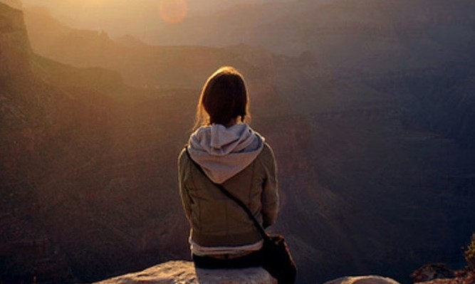 静けさの中、山を見下ろし祈る女性