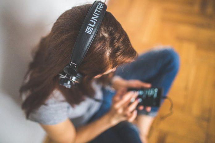 ヘッドホンをつけ、音楽を聴く女子