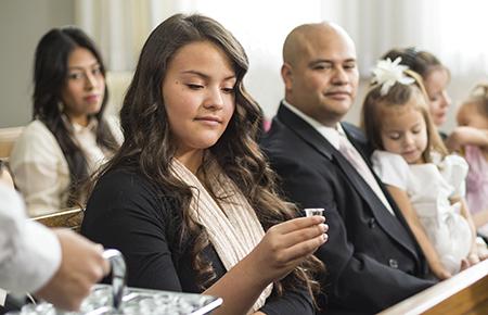 教会で聖餐の水をとる若い女性と家族