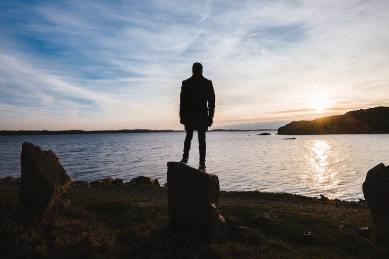 海を見つめ岩の上に立つ人の姿