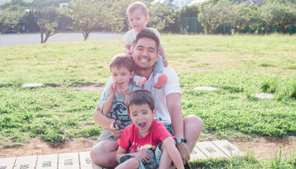笑顔の父親と子供3人が縦に座って並んでいる様子